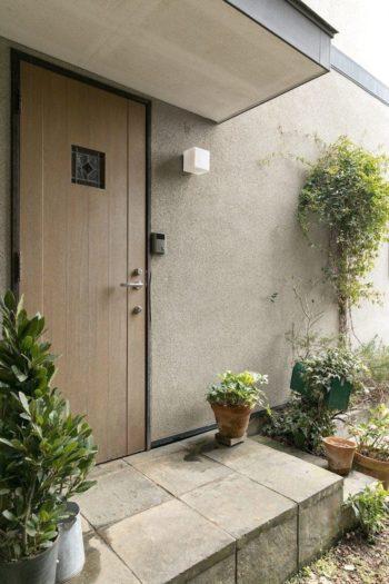 玄関にも豊かな植栽が。ドアにはめられたステンドグラスは、お父様が福岡でオーダーしてつくってもらったもの。