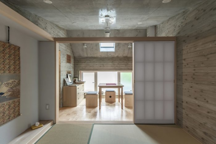 和室からスノコペースと呼ばれる空間を見る。杉板型枠を使って打設したコンクリートの壁面が和室としっくりと合う。