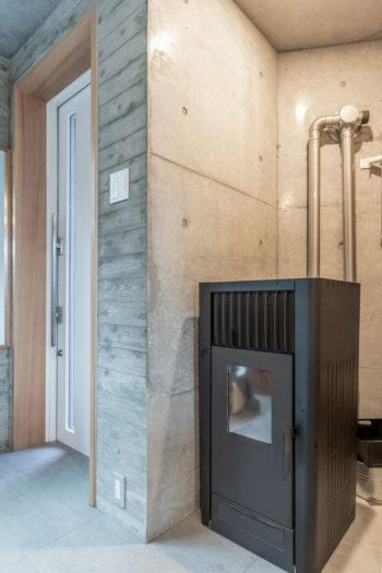 玄関脇に置かれたペレットストーブ。床下へと回した暖気が小上がりに設けたスリットから出る。