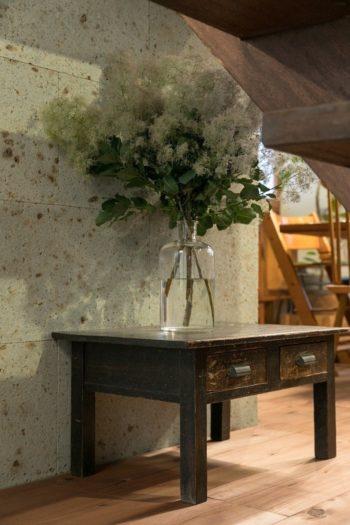 古家具と大谷石とスモークツリーが美しい。「花はこの家に越してからよく飾るようになりました」とひろみさん。