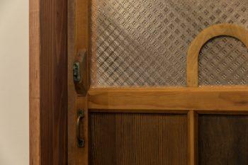 透かしガラスがキュートなキッチンの横に作ったパントリーの扉。大越宅にはたくさんの古い建具が使われている。