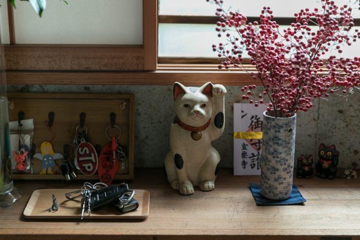 玄関の下駄箱の上に招き猫。鍵をかけておくフックや、クルマのキーを置くトレイがバランスよく。