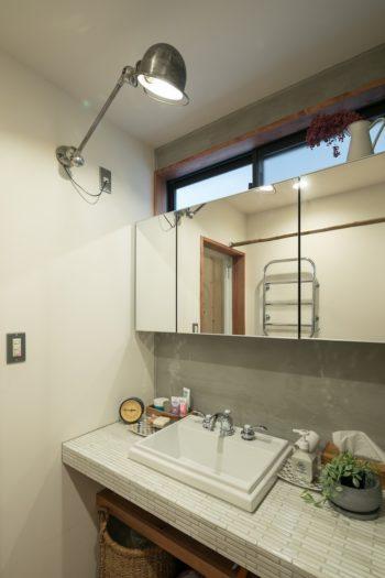 フランスのジェルデライトを壁付けにして、洗面の照明器具にしている。洗面台はタイル貼りに。鏡の上に明り取りの窓を新設。