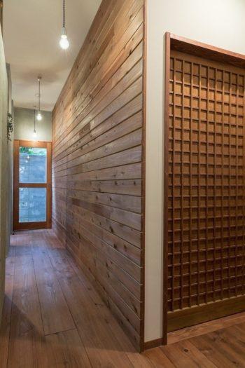 洗面所のドアの格子と、勝手口に通じる板を横に張った壁とフローリングの木の表情が豊か。