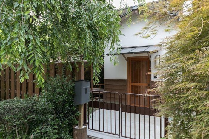 緑豊かな遊歩道沿いの大越邸。庭の枝垂れ桜は30年前に植えたものだそう。