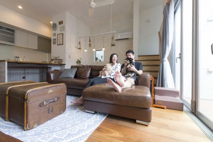 「2人がゆったり座れるソファを選びました」という大型のソファは、建設途中にお台場の家具屋で購入。ローテーブルとして使用しているアンティークのトランクともぴったり。奥さまが独身時代から飼っているソラくん(7歳・右)と、結婚後に飼い始めたマメくん(5歳・左)と共に、ソファで過ごすことが多いそう。