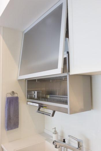 「食洗機の臭いが苦手」(ご夫妻)と、食器乾燥機を設置。昇降機能付きなので、「来客のときはすぐに隠せて便利です」(奥さま)