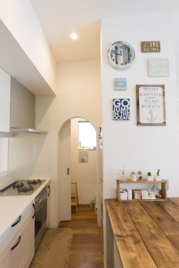 アーチ型の入り口の奥がパントリー。キッチンから丸見えにならないように扉を設置。