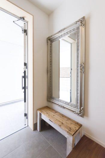 玄関のアンティークな鏡は奥さまの持ち込み。椅子はダイニングテープル等と同じパイン材の造作。
