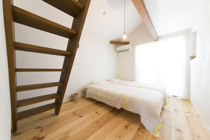 2階の寝室。「どんどんそぎ落としていったら裸電球になってしまいました」と千絵さん。はしごの先はロフトになっている。