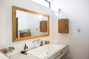実験シンクを用いた、レトロ感のある洗面所。モルタルと木のミックス感が心地いい。