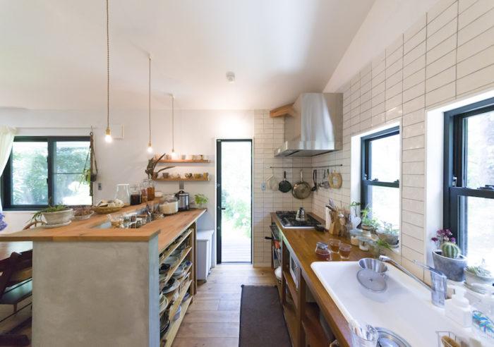 すべてオーダーのキッチン。左のカウンター下には、無印良品のシェルフがすっぽり収まるようサイズを測って注文。自ら合う色に塗り替えたそう。奥のドアはウッドデッキと実家に続く小道へ。