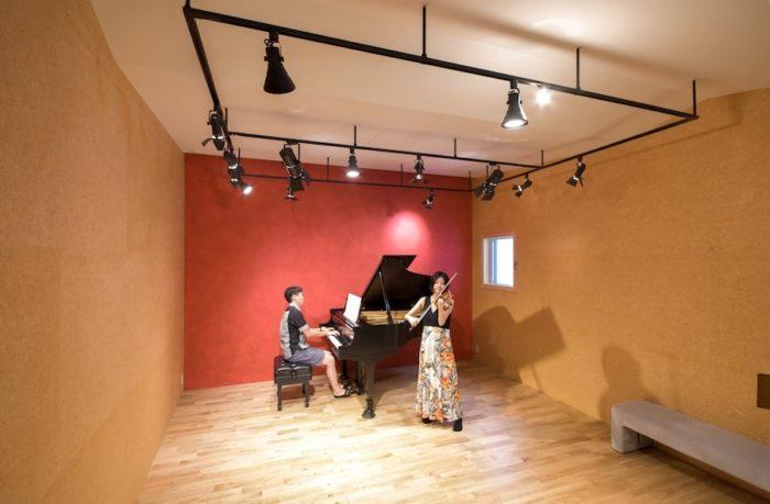 音響を考慮して天井部分がアップダウンしている。ふだんは吸音マットも使用する。正面の壁はスタッコ仕上げで藤﨑さんの好きな赤系統の色が塗られている。