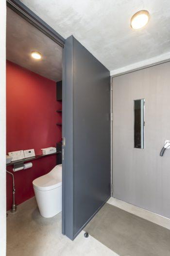 1階に設けられたトイレの壁も藤﨑さんの好きな赤に塗られている。右はスタジオのドア。