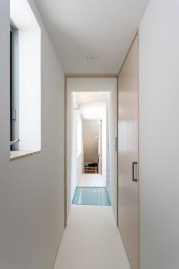 3階廊下部分を寝室側から見る。奥に本棚が見える。床がガラスの部分が吹き抜けになっている。