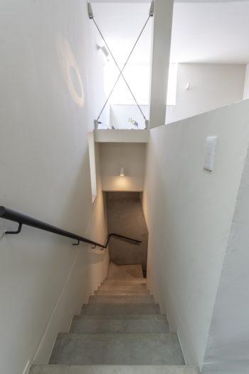 2階から見下ろす。階段を下って右側に2、3階のプライベート空間と仕切るためのドアが設けられている。