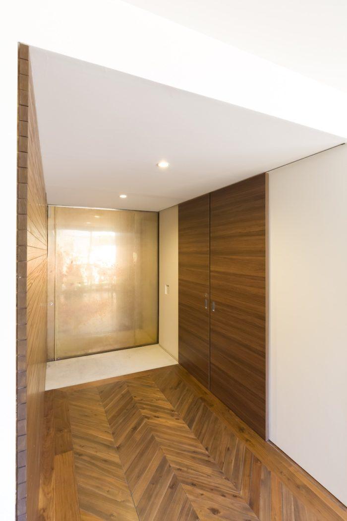 真鍮をあしらった玄関扉を入ると土間風の玄関。1階の床はアカシアの木をウォールナット色に染色してフレンチヘリンボーン張りに。