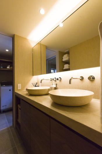 洗面所にも人工大理石の天板を使用。素材の上質感や照明の工夫がホテルライクな雰囲気を生んでいる。