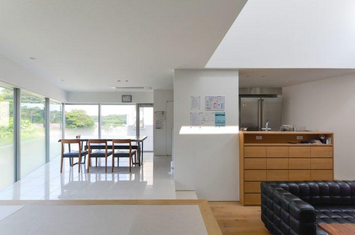 小上がりの畳の上から見る。畳の色はフローリングの色に合わせてセレクト。キッチンは子どもたちの居場所が見えるようにとの奥さんの要望で対面式に。奥の冷蔵庫は開く向きが逆のものを2つ組み合わせている。