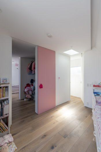 上のお嬢さんの部屋と姉妹共有のウォークインクローゼットを仕切る戸はピンク色。入口付近にトップライトが設けられている。