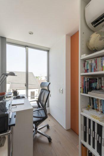 Nさんの書斎と夫婦のウォークインクローゼットの間の戸はオレンジ。書斎は3畳と当初より狭くなったが居心地がいいという。