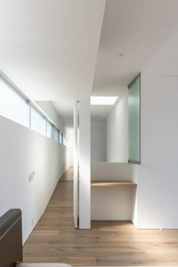 主寝室からスロープ状になった廊下を見る。階段と通ずる開口も設けられている。