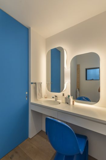 洗面所にはドアの色に合わせて青色の椅子が置かれている。