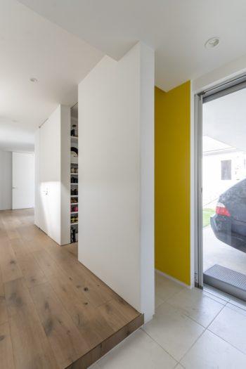 手前の玄関とシューズクローゼットの間の壁は黄色に塗られている。右のガラスドアからガレージに出ることができる。