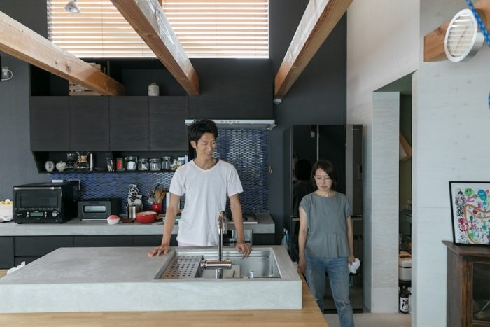 モルタルの造作キッチン。テーブルよりキッチンの高さを上げることで、洗い物などがしやすい高さに。お客様と話ができるキッチンだ。