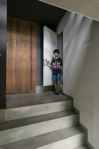 左の杉板のドアが玄関。涼くんが顔を覗かせているドアが、インナーテラスへと続く外階段につながっている。
