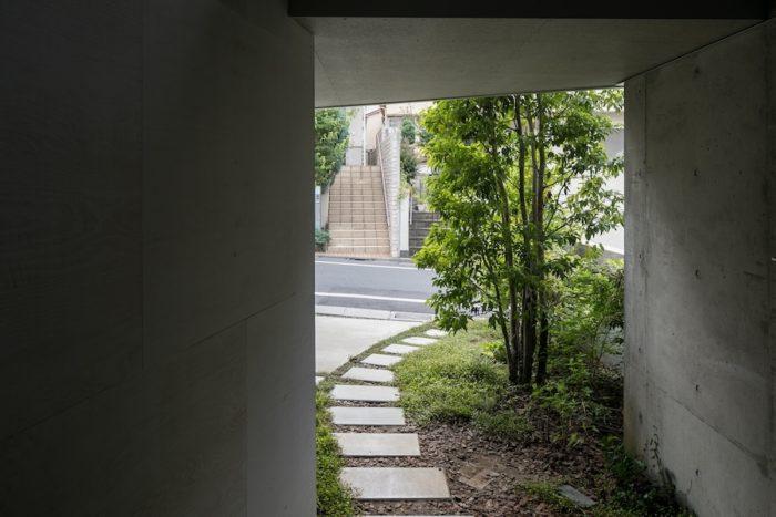 玄関から外へ。曲線を描く敷石や、植栽にも物語を感じるアプローチ。
