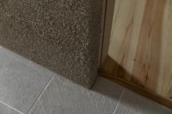 バスルームは床のタイルにも壁材にも陰影があるものをチョイス。廊下は無垢のフローリング。