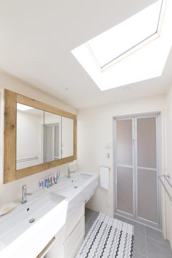 バスルームなどの水回りは2階へまとめた。天窓からたっぷりの光が入る。鏡の枠は古材を使用。