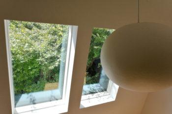 階段途中から開口を通してカエデの木が見える。右の照明はMOONという名の製品で質感にもこだわって購入したもの。