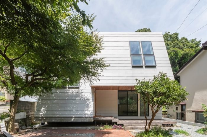 「この形の明るい印象の新しい家がここにあるとたぶんこの一帯が明るく感じられるのでは」とKさんが思ったという外観にはガルバリウム鋼板が使われている。使い勝手がいいという、右側の縁側的な場所を経て左側の玄関ドアにいたる。