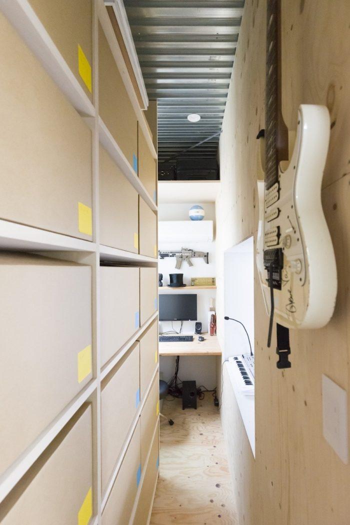 収納には段ボール箱を活用。細い廊下の向こうに小さな趣味の部屋が。
