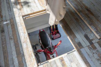 バイクを上げ下げするために床を取り外すことができるようにしている。