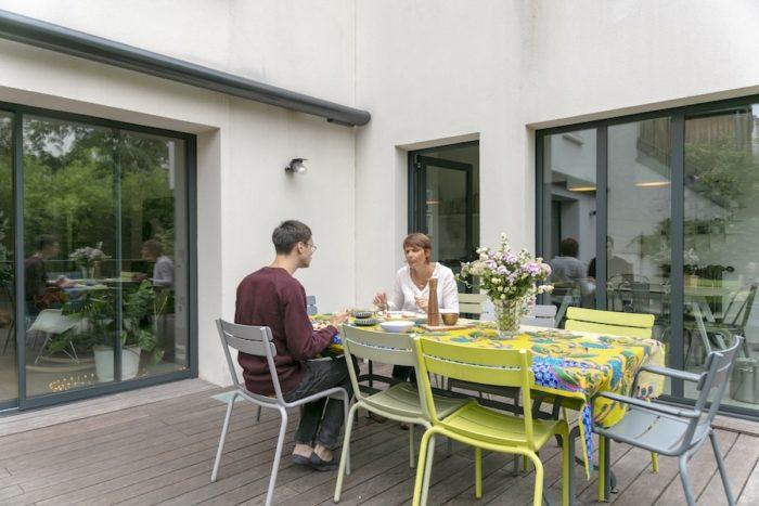 庭のテーブルに花を飾りテーブルクロスをかけて、リビング感を演出。テーブルクロスは切りっぱなしのアフリカプリント布。