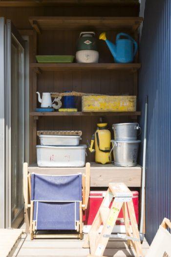 テラスの軒下の物入れ。給食用のアルミの運搬容器は、キャンプに行くときにも重宝しているそう。