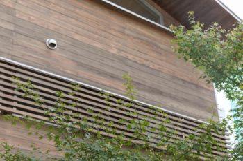 窓につけた木製のルーバーは、アルミサッシの無機的な雰囲気を消す意匠的な役割と、目隠しや日差しカットという実用的な役割を併せ持つ。