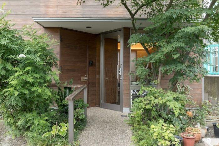 生き生きと枝を伸ばす植栽が印象的なエントランス。右のガラス扉は美容室に、左の木製扉は住居スペースにつながる。アプローチと玄関土間は、趣のある豆砂利洗い出し仕上げ。
