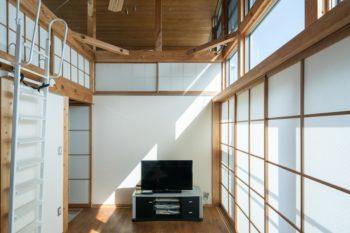明るい光がたっぷり入るリビング。左の梯子を上がると大空間のロフトが広がり、奥の障子の向こうは半階上がった房子さんの寝室になっている。