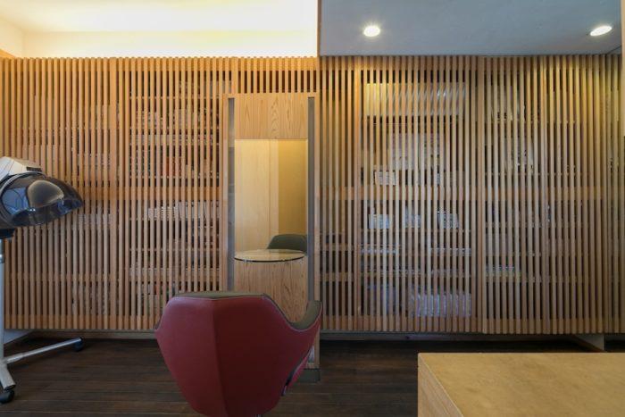 理子さんと金田さんが特にこだわったのは、壁一面の美しい格子。中には美容室で使うさまざまな物が収まる。セット面ミラーも金田さんのデザイン。