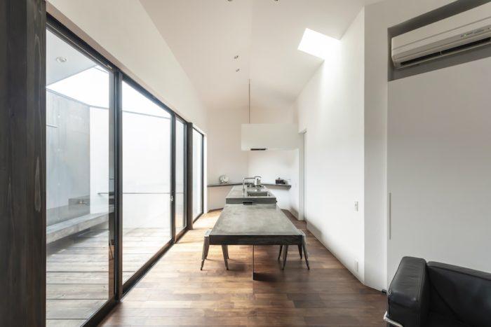 キッチンとダイニングテーブルを一体のものとしてデザイン。木の上にモルタルを塗りつけ、さらに塗装をした上から防水塗料を塗っている。テーブル部分は鉄板の壁に合わせて脚の部分を鉄板にしている。