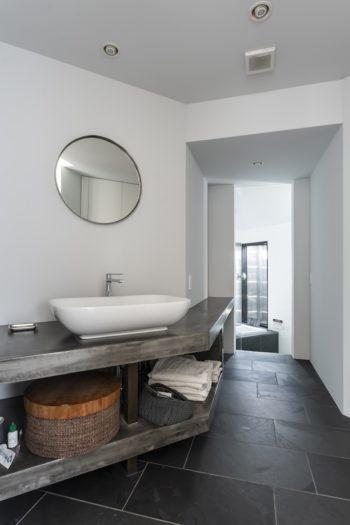 リビングに面した扉を開けると水回り空間が現れる。奥の浴室に行くには手前の空間から左に折れつつ下りる。