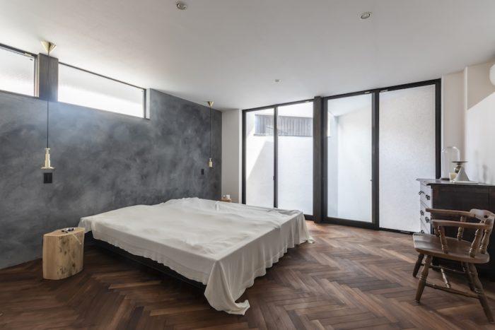 広いスペースに大きなベッドを置きたかったという寝室。床は夫妻の希望でヘリンボーンに。壁は一面だけジョリパット仕上げ。天井から吊るされた照明はトム・ディクソンの製品。丸太をそのままナイトテーブルにしている。