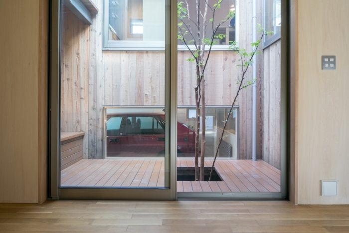 ガルバリウムの外観に対し、内側は素朴な加工を施したレッドシダーの壁面。中庭越しに愛車が見える。