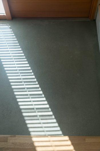 玄関はモルタルをコーティングしてある。ブラインド越しの光が美しい。