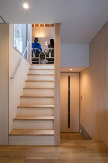 ダイニングとキッチンは通常より低めの2階に。階段を昇ったところに小さめの扉をつけ、エアコンの冷気が1階に逃げない工夫も。玄関からの視線を遮ることもできる。