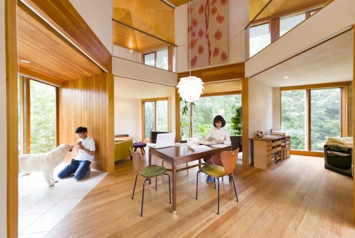 白い壁や天井は珪藻土、板張りの壁、木製の建具など身体に優しい自然素材を使用。ダイニングは真知子さんの仕事場にもなる。近くに和憲さんとピークくんがいるのが日常の光景。